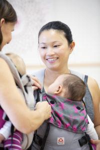 Frau mit Baby in Babytrage zur Beratung
